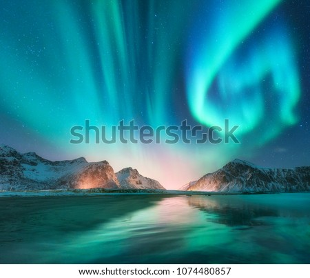 Aurora borealis in Lofoten islands, Norway. Aurora. Green northern lights. Starry sky with polar lights. Night winter landscape with aurora, sea with sky reflection, stones, beach and snowy mountains #1074480857