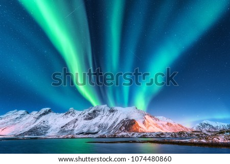 Aurora borealis. Lofoten islands, Norway. Aurora. Green northern lights. Starry sky with polar lights. Night winter landscape with aurora, sea with sky reflection and snowy mountains.Nature background Royalty-Free Stock Photo #1074480860