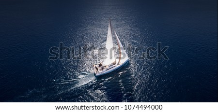 Sailing ship yachts with white sails at opened sea. Aerial - drone view to sailboat in windy condition. #1074494000