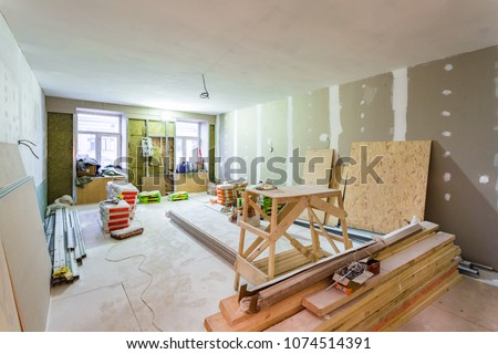 Working process of installing metal frames for plasterboard -drywall - for making gypsum walls  in apartment is under construction, remodeling, renovation, extension, restoration and reconstruction.  Royalty-Free Stock Photo #1074514391