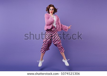 Full-length shot of glad curly woman in striped pants jumping on purple background. Indoor portrait of wonderful girl in sunglasses fooling around in studio. #1074521306