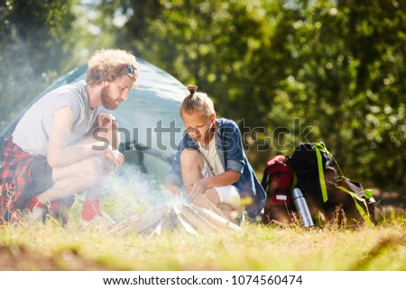 Two young backpackers making bonfire by pile of woods during their backpack trip in the forest #1074560474
