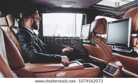 Young handsome businessman is sitting in luxury car. Serious bearded man in suit and glasses #1074562073