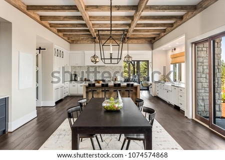 Stunning Dining room and Kitchen in New Luxury Home. Wood beams and elegant pendant lights accent the beautiful open floor plan, dining room, and kitchen. #1074574868