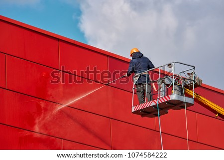 Worker wearing safety harness washes wall facade at height on modern building in a crane. Royalty-Free Stock Photo #1074584222