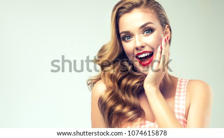 Woman with red lips and nails surprise holds cheeks by hand .Beautiful girl  with curly hair surprised and shocked looks on you . Presenting your product. Expressive facial expressions #1074615878