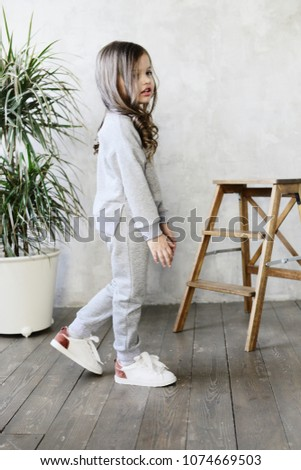 Little stylish girl in a gray suit #1074669503