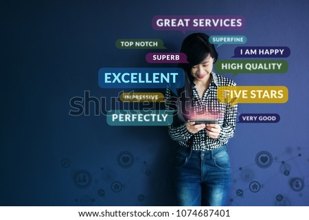 Customer Experience Concept. Soft focus of Happy Client standing at the Wall, Smiling while using Smartphone. Surrounded by Positive Review in Speech Bubble and Social Network icons Royalty-Free Stock Photo #1074687401
