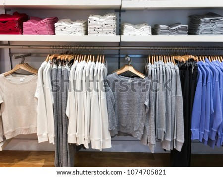 female , clothing set of on the racks in clothing store    #1074705821