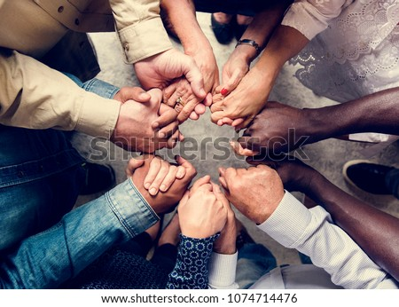 Group of diverse hands holding each other support together teamwork aerial view Royalty-Free Stock Photo #1074714476