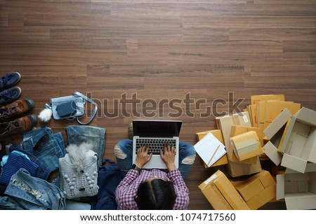 Top view of women working laptop computer from home on wooden floor with postal parcel, Selling online ideas concept #1074717560