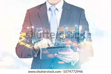 Close up of an unrecognizable businessman working with his tablet computer. A night cityscape background. Toned image double exposure #1074772946