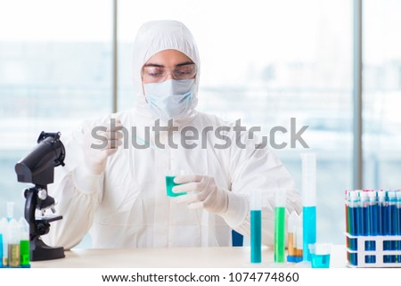 Young chemist student working in lab on chemicals #1074774860