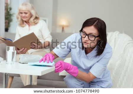 No dust. Elder woman reading book while responsible caregiver cleaning surface #1074778490