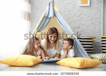 Nanny and little children reading book in tent at home #1074808340