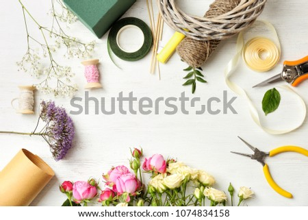 Florist equipment with flowers on wooden background, top view Royalty-Free Stock Photo #1074834158