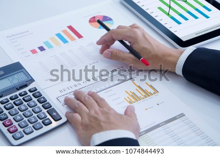 Businessman is deeply reviewing a financial report for a return on investment or investment risk analysis. #1074844493