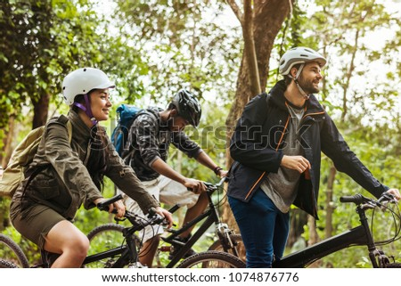 Group of friends ride mountain bike in the forest together #1074876776