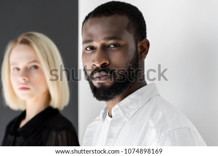 multicultural couple looking at camera near black and white wall #1074898169