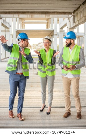 Team of successful young architects and business partners checking work progress on a construction site. Architecture and teamwork concept. #1074901274