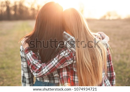 Two young woman looking on the sunset and hugging. Best friends #1074934721