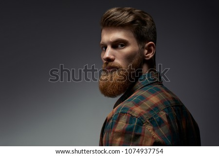 Perfect beard. Close-up of young bearded man standing against grey background #1074937754