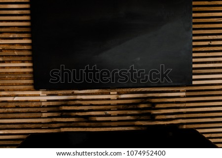 Black board on the background of a wooden wall #1074952400