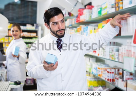 Confident man pharmacist is standing with medicines in drugstore #1074964508