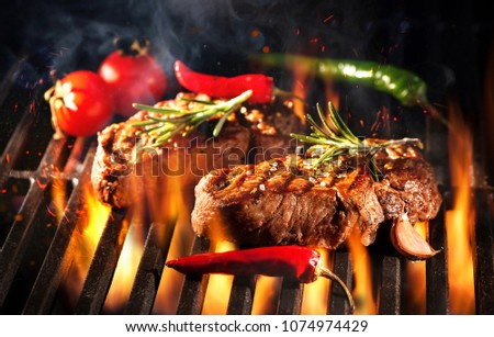 Beef steaks on the grill with flames and smoke #1074974429