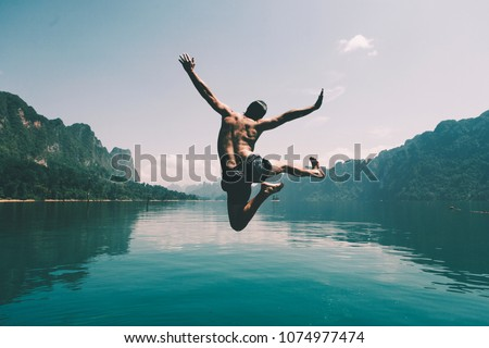 Man jumping with joy by a lake Royalty-Free Stock Photo #1074977474