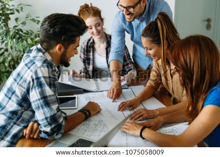 Image of business partners discussing documents and ideas #1075058009