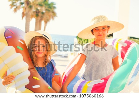 Two small girls with inflatable toys on the beach. Summer vacation and traveling concept #1075060166