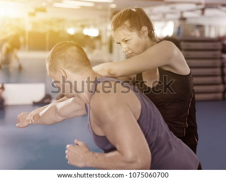 Nice female is fighting with trainer on the self-defense course for woman in sport club Royalty-Free Stock Photo #1075060700