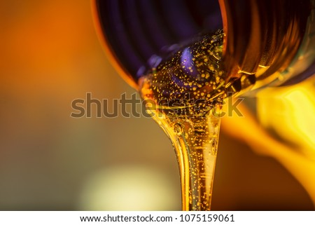 Liquid stream of motorcycle motor oil flows from the neck of the bottle close-up. #1075159061