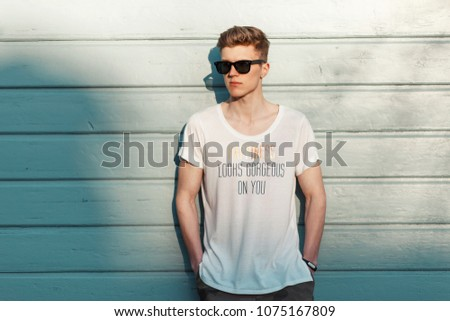 Stylish young man with sunglasses in a fashion white T-shirt posing near a blue wooden wall on the beach #1075167809