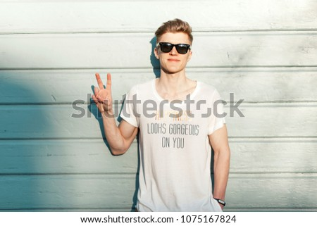 Fashion young man hipster with sunglasses and a fashionable white T-shirt showing a peace sign near a blue wooden wall on a sunny day. Happiness looks gorgeous on you #1075167824
