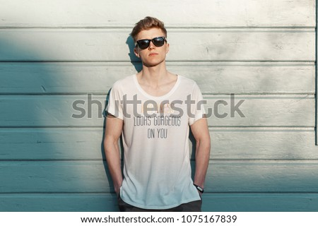 Handsome young stylish model man in sunglasses with a stylish white t-shirt stands near a wooden blue wall #1075167839