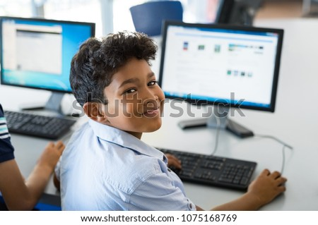 Young happy schoolboy using computer. Arab child learning to use computer at elementary school. Portrait of smiling middle eastern kid looking at camera while surfing the net in school library. #1075168769