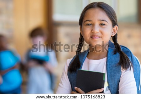 Smiling student girl wearing school backpack and holding exercise book. Portrait of happy asian young girl outside the primary school. Closeup face of smiling hispanic schoolgirl looking at camera. #1075168823