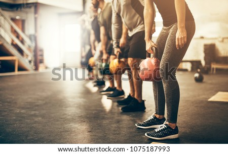 Fit group people in exercise gear standing in a row holding dumbbells during an exercise class at the gym #1075187993