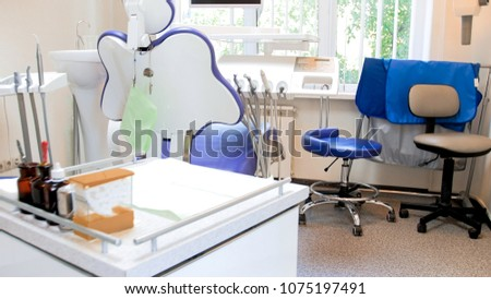 Empty chair in dentist office with big window #1075197491