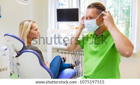 Male dentist wearing on protective mask before treatment #1075197515