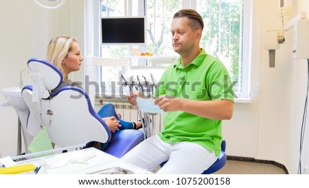 Dentist getting ready for medical treatment and wearing protective mask #1075200158