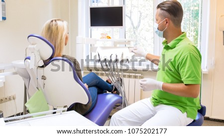 Male dentist adjusting height of dentist chair in modern clinic #1075202177