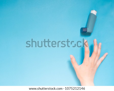 Asthma and COPD disease concept. Young female hand trying to reach blue asthma inhaler for relief asthma attack symptoms on light blue background with copy space for text. Top view. Minimal style. Royalty-Free Stock Photo #1075212146
