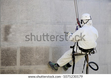 Rope access facade maintenance; A worker wearing a protective gear cleaning a stone exterior with sandblasting equipment #1075230179