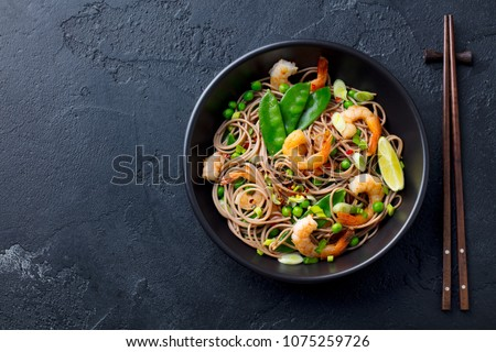 Stir fry noodles with vegetables and shrimps in black bowl. Slate background. Top view. Copy space. #1075259726