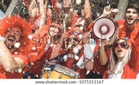 Friends football supporter fans cheering with confetti watching soccer match event at stadium - Young people group with red t-shirts having excited fun on sport world championship concept #1075311167