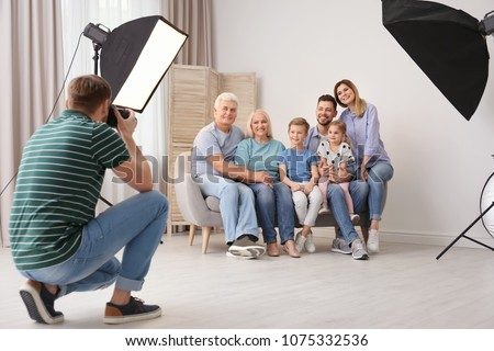 Professional photographer taking photo of family on sofa in studio