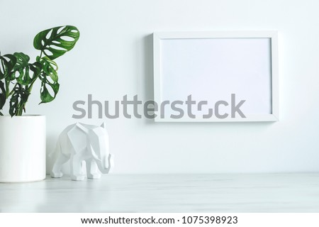Design white space with mock up photo frame, plant and elephant figure. Minimalist concept of stylish interior.